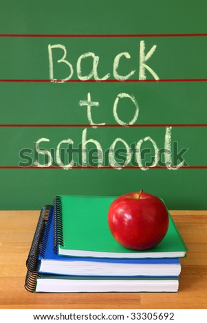 Exercise books and red apple on desk with back to school written on the chalkboard - stock photo
