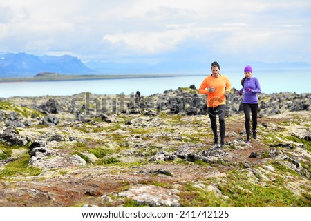 Exercise running sport. Runners on cross country trail run outdoors working out. Fit young fitness model man and asian woman training together outside in mountain nature on Snaefellsnes, Iceland. - stock photo