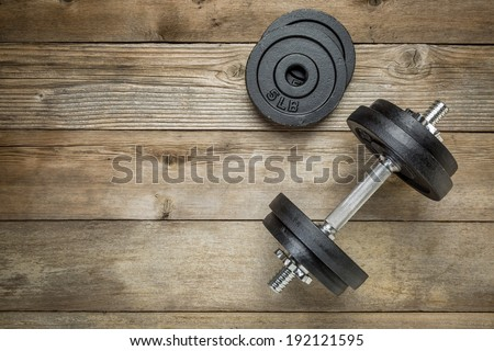 exercise weights - iron dumbbell with extra plates on a wooden deck - stock photo