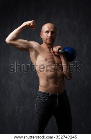 Exercise With Kettle Bell. Muscular  Men Doing Swing Exercise With Kettle bell. Model posing in studio on dark background. - stock photo