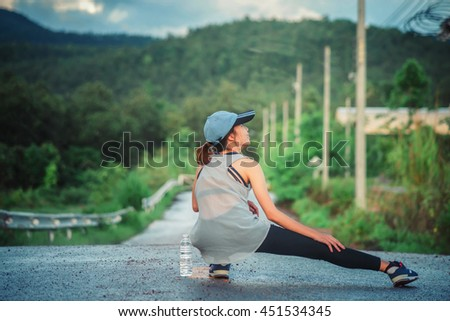 Exercise woman stretching hamstring leg muscles during outdoor running workout.  - stock photo