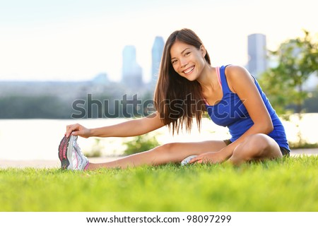 Exercise woman stretching hamstring leg muscles during outdoor running workout. Smiling happy mixed race Asian Chinese / Caucasian sport fitness model in city park. - stock photo