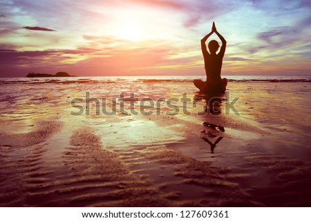 exercises on the beach at sunset - stock photo
