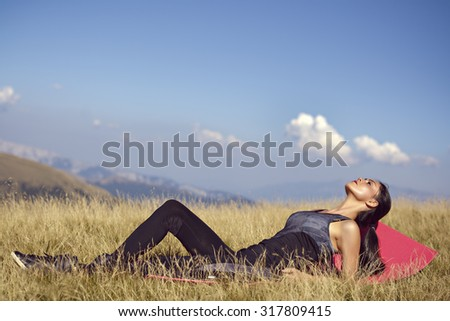 Exercising fitness woman doing exercises in nature.  Fit female Asian Caucasian athlete sport model