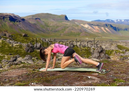 Exercising fitness woman doing exercises in nature. Girl doing mountain climbers exercise training outside in amazing landscape on Iceland. Fit female Asian Caucasian athlete sport model . - stock photo