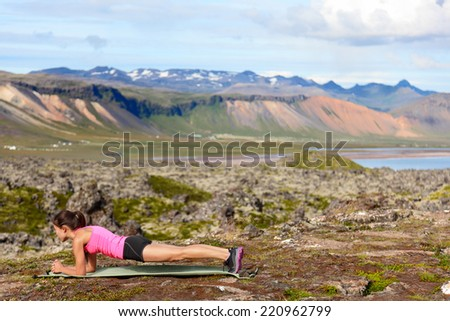 Exercising fitness woman doing plank in nature training core outside in amazing nature landscape on Iceland. Fit female sport model girl training outdoors. Mixed race Asian Caucasian athlete. - stock photo