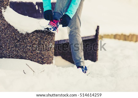 Exercising girl tying sholeaces. Young female in park. Fitness outdoors fashion shoes concept.