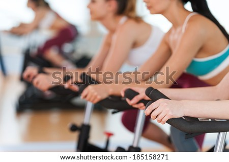 Exercising on gym bikes. Cropped image of tree young women in sports clothing exercising on gym bicycles - stock photo
