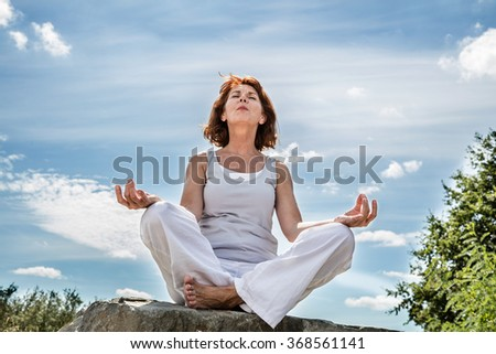 exercising outdoors - beautiful middle aged woman sitting on a stone in yoga lotus position, wearing white, seeking for serenity over blue sky,low angle view - stock photo