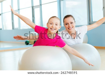 Exercising together is fun. Cheerful mother and daughter exercising with fitness balls and looking at camera - stock photo