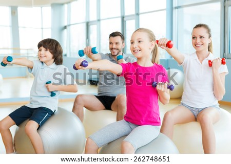Exercising together is fun. Happy sporty family exercising in sports club together