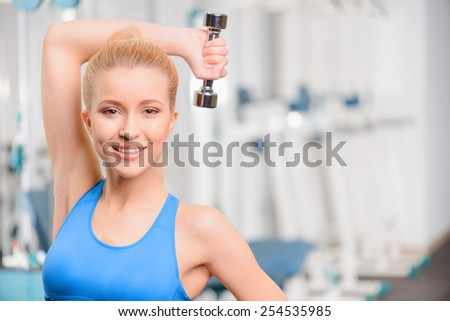 Exercising with dumbbells. Beautiful young woman in sports clothing exercising with dumbbells and smiling while sitting in health club   - stock photo