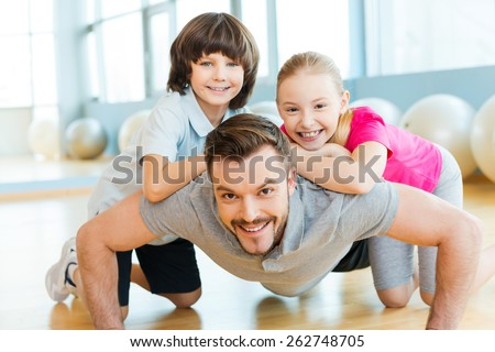 Exercising with father. Happy little children bonding to their father doing push-ups in sports club - stock photo