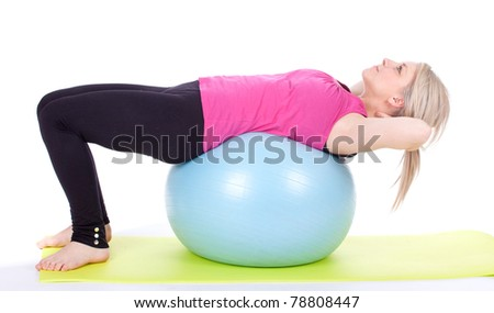 exercising young woman on big blue ball