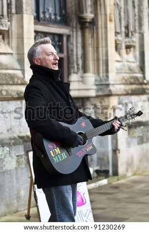 EXETER - DECEMBER 16: Billy Bragg performing in front of Exeter Cathedral as part of an afternoon of music and performace at Occupy Exeter Camp on December 16, 2011 in Exeter, UK - stock photo