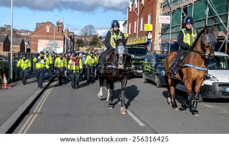 EXETER, ENGLAND - FEBRUARY 21, 2015: Devon and Cornwall Police escort football fans away during the police operation at the League 2 football match between Exeter City FC and Plymouth Argyle FC  - stock photo