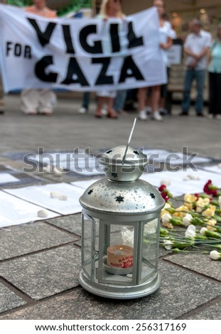 EXETER, ENGLAND - JULY 15, 2014: A candle is lit for the dead in Gaza during the Peace Vigil for Gaza in Exeter's Princesshay Square. - stock photo