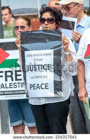 EXETER, ENGLAND - JULY 15, 2014: Peace campaigner hold a sign, which demands Justice and peace during the Peace Vigil for Gaza in Exeter's Princesshay Square. - stock photo