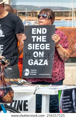 EXETER, ENGLAND - JULY 15, 2014: Peace protester hold a sign, which says 'End the Siege on Gaza' during the Peace Vigil for Gaza in Exeter's Princesshay Square. - stock photo