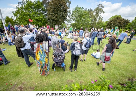 EXETER, ENGLAND - JUNE 13, 2015: The crowd look on during the Devon 'End Austerity NOW!' Rally in Northernhay Gardens, Exeter on June13th, 2015 in Exeter, UK