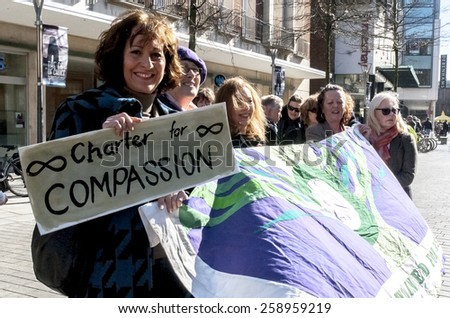 EXETER, ENGLAND - MARCH 7, 2015: Devon United Women hold a banner during the Walk for Peace through the city of Exeter to celebrate International Women's Day. - stock photo