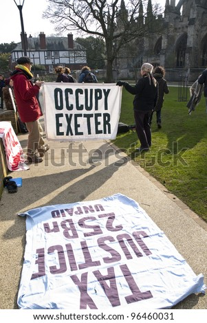 EXETER - FEBRUARY 11: Occupy Exeter activist hold up an Occupy Exeter banner on Exeter Cathedral green during the Occupy Exeter leaving the Exeter Cathedral Green event in Exeter. - stock photo