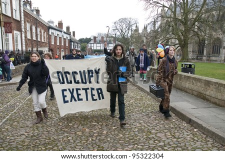EXETER - FEBRUARY 11: Occupy Exeter activist march out of the Cathedral grounds during the Occupy Exeter leaving the Exeter Cathedral Green event in Exeter  on February 11, 2012 in Exeter, UK. - stock photo