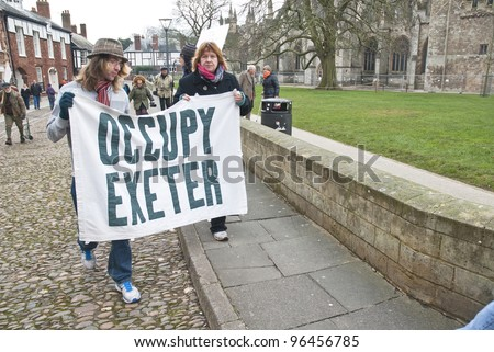 EXETER - FEBRUARY 11: Occupy Exeter activist march out of the Cathedral grounds EXETER - FEBRUARY 11: Occupy Exeter leaving the Exeter Cathedral Green  in Exeter on February 11, 2012 in Exeter, UK - stock photo