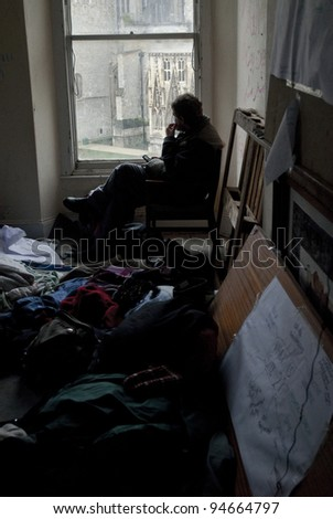 EXETER - FEBRUARY 4: Occupy Exeter activist sits in the Guard Room of Occupy Exeter site 2 and looks out over Exeter Cathedral Green and the old Occupy Exeter camp on February 4, 2012 in Exeter, UK - stock photo