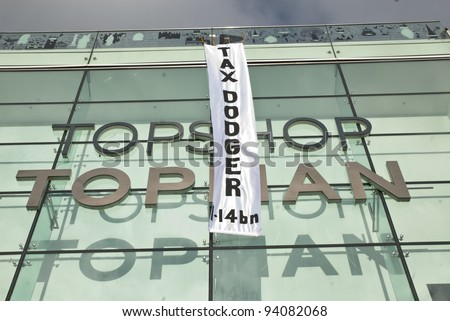"EXETER - JANUARY 28: The Occupy Exeter banner saying ""Tax Dodger 1.4bn"" hangs down the front of the Exeter Branch of Topshop  on January 28, 2012 in Exeter, UK - stock photo"