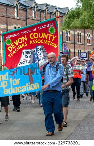 EXETER - JULY 10: A man from the National Union of Teachers walks with protesters during the public sector workers national day of action in Exeter City Centre on July 10,  2014 in Exeter, Devon, UK - stock photo