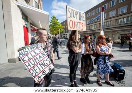 EXETER - JULY 8: Demonstrators hold up placards at the Exeter Budget Day Action #AusterityKills in Exeter City Centre on july 8th, 2015 in Bedford Square, Exeter, UK