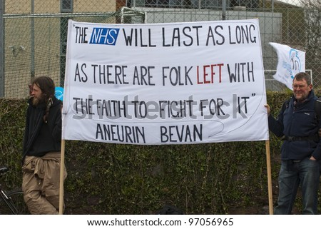 EXETER - MARCH 7: Protestors hold up a sign , during the NHS reform protest outside the Royal Devon & Exeter Hospital on March 7, 2012 in Exeter, UK - stock photo