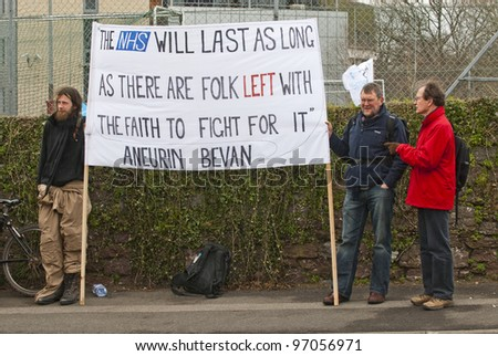 EXETER - MARCH 7: Protestors hold up a sign, during the NHS reform protest outside the Royal Devon & Exeter Hospital on March 7, 2012 in Exeter, UK - stock photo