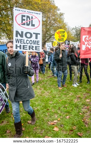 EXETER - NOVEMBER 16: A lady holds up a 'EDL Not Welcome Here', with a stop the Nazis sign behind her during the Exeter Together march and diversity festival on November 16, 2013 in Exeter, Devon, UK - stock photo
