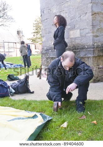 EXETER - NOVEMBER 12: Justine Freeman is the first one to pitch his tent at the occupy Exeter site of Exeter Cathedral green.  on November 12, 2011 in Exeter City Centre. - stock photo