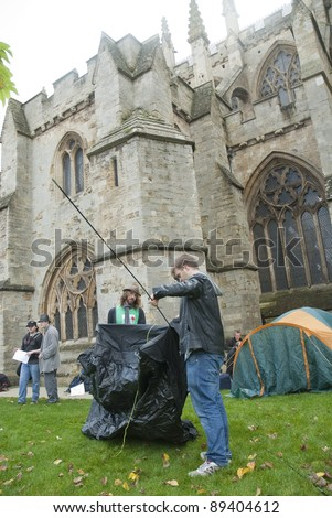 EXETER - NOVEMBER 12: Occupy Exeter supporters and participants erect their tents at the occupy Exeter site of Exeter Cathedral  on November 12, 2011 in Exeter City Centre. - stock photo