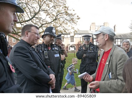 EXETER - NOVEMBER 12: Police film occupy Exeter organiser Ghee Bowman talking with acting dean Carl Turner at the occupy Exeter site of Exeter Cathedral on November 12, 2011 in Exeter City Centre - stock photo