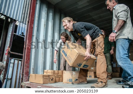 EXETER, UK - MARCH 27: Bookcycle volunteers pick up boxes onto the back of the container during the loading for books bound for Ghana at the BookCycle warehouse on March 27, 2014 in Exeter, Devon, UK