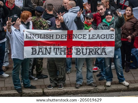 EXETER, UK - NOVEMBER 16: English Defence League members hold up a 'Ban the Burka' banner during the English Defence League march and rally November 16, 2013 in Exeter, Devon, UK