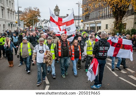 EXETER, UK - NOVEMBER 16: English Defence League members march along the street during the English Defence League march and rally November 16, 2013 in Exeter, Devon, UK - stock photo