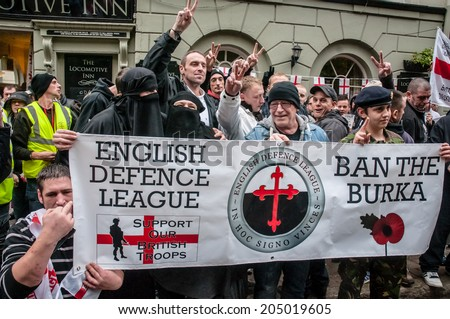 EXETER, UK - NOVEMBER 16: English Defence League supporters hold up a banner during the English Defence League march and rally November 16, 2013 in Exeter, Devon, UK