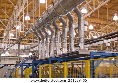 Exhaust hood with spiral air duct for ventilation in production process - stock photo