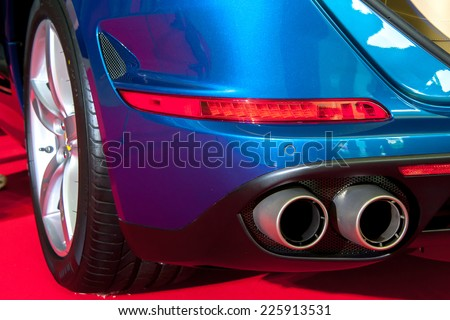 exhaust pipe of a blue car - stock photo