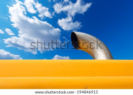 Exhaust Pipe on Blue Sky / Detail of an metallic exhaust pipe of an orange excavator on blue sky with clouds - stock photo
