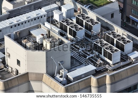 Exhaust vents of industrial air conditioning and ventilation units. Skyscraper roof top in Tokyo, Japan. - stock photo