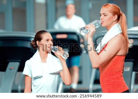 Exhausted after workout. Attractive mature woman and her teenage daughter in sports clothing drinking water while standing in sports club with a towel on their shoulders - stock photo