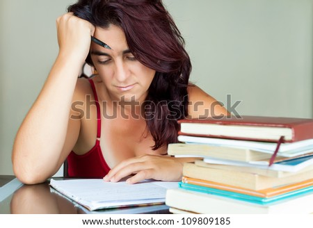Exhausted and overworked hispanic woman studying with a pile of books on her desk