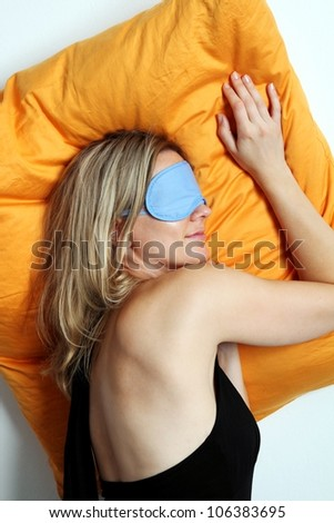 Exhausted attractive blonde woman taking a mid day rest and sleeping on an orange cushion in a mask - stock photo