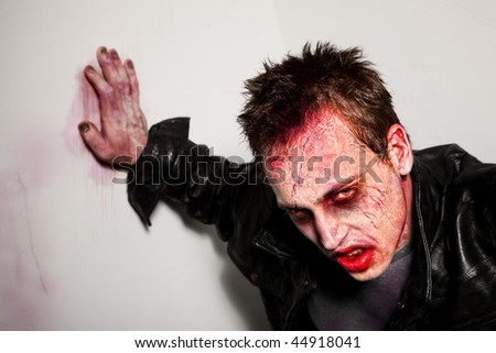Exhausted bloody zombie leaning against a wall - stock photo